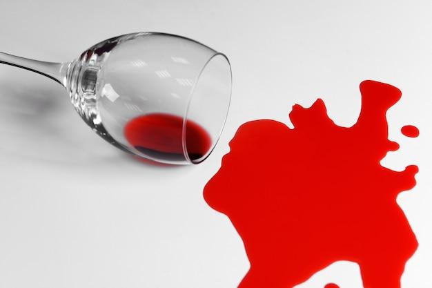 Vino rosso versato dal bicchiere su bianco