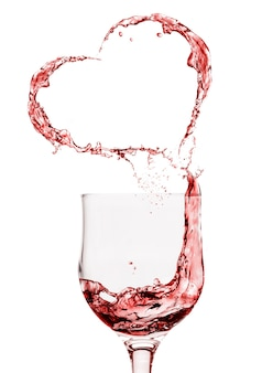 Spruzzi di vino rosso che formano cuore isolato su bianco