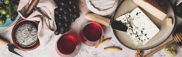 Vino rosso con assortimento di salumi sul backgrou di cemento rustico