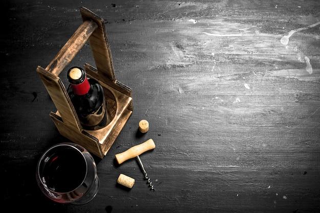Vino rosso con cavatappi e sughero. sulla lavagna nera.