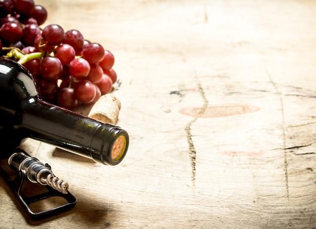 Vino rosso con un cavatappi, uva e tappi su fondo in legno