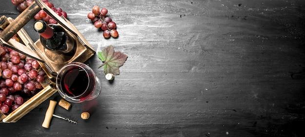 Vino rosso con uve fresche in una scatola sulla lavagna nera