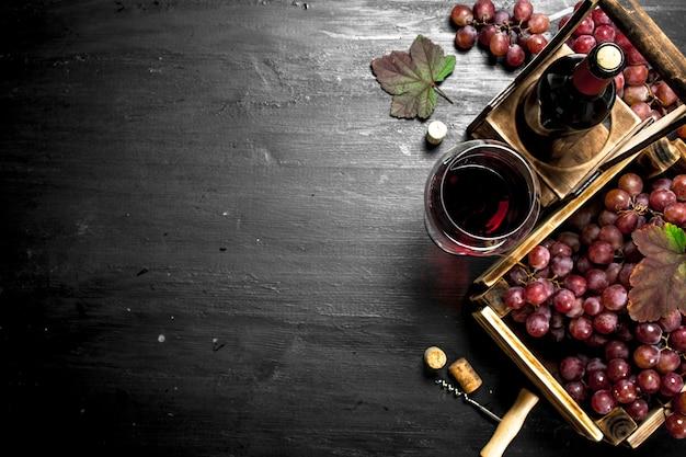 Vino rosso con uve fresche in cassetta. sulla lavagna nera.