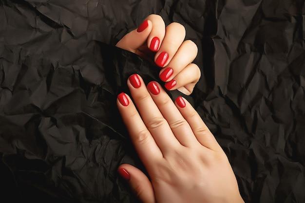 Manicure della donna rossa sui precedenti neri di arte. colore seducente. superficie delle unghie lucide.