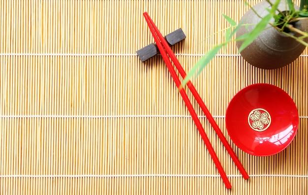 Bacchette di legno rosso e ciotola rossa per sushi su sfondo opaco di bambù copia spazio