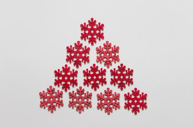 Fiocchi di neve rossi artigianali in legno disposti come un triangolo sulla superficie bianca