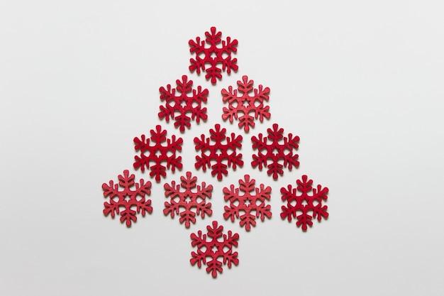 Fiocchi di neve artigianali in legno rossi disposti come albero di natale su superficie bianca