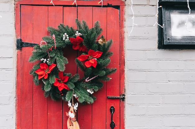 Porta in legno rossa decorata con ghirlanda di natale.