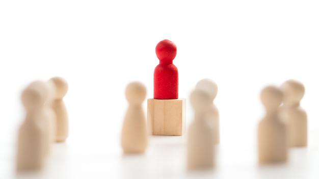 La figura in legno rosso in piedi sulla scatola mostra influenza e potere. concetto di leadership aziendale per team leader, vincitore di una competizione di successo e leader con influenza