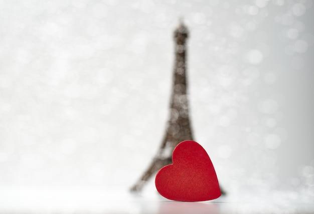 Cuore di legno rosso davanti alla piccola torre eiffel. concetto di san valentino.