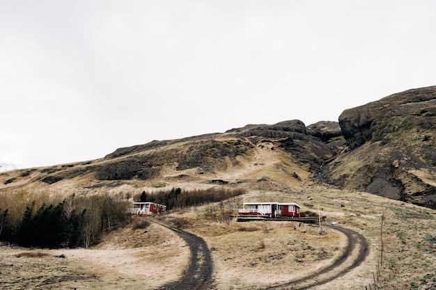 Una casa di legno rossa ai piedi di una montagna in islanda