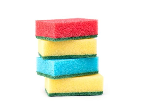 Spugne rosse, gialle e blu per lavare i piatti isolate su fondo bianco white