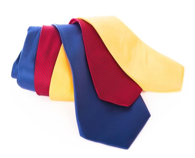 Cravatte rosse gialle e blu. cravatta da lavoro in seta arrotolata su sfondo bianco
