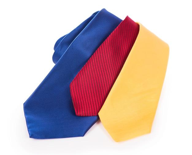 Cravatte rosse gialle e blu. cravatta da lavoro in seta arrotolata su sfondo bianco Foto Premium