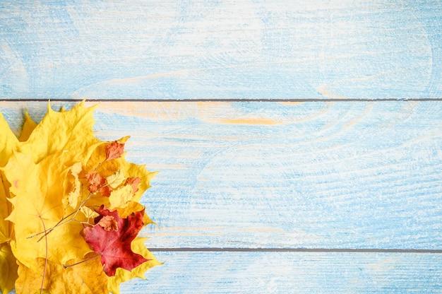Foglie di acero autunnali asciutte rosse e gialle e ramoscelli autunnali su un tavolo o uno sfondo di legno blu. materiali autunnali per la creatività e l'artigianato dei bambini. spazio per il testo