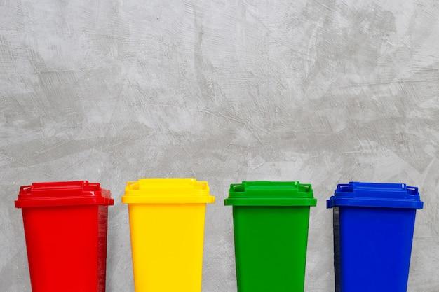 Pattumiere rosse, gialle, verdi e blu. sfondo muro di cemento copia spazio