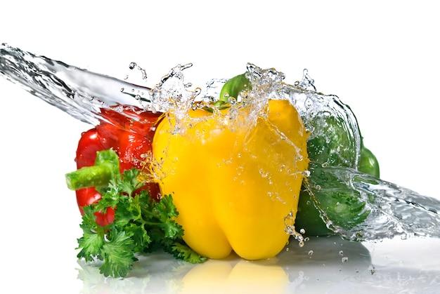 Peperone rosso, giallo, verde e prezzemolo con spruzzi d'acqua isolati su bianco