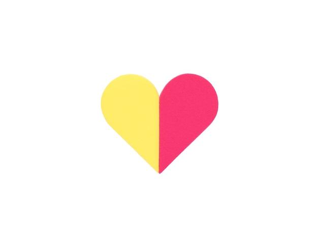 Spugna rossa e gialla a forma di cuore isolata su una superficie bianca