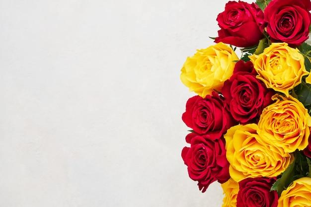 Bouquet di rose rosse e gialle con copia spazio come sfondo