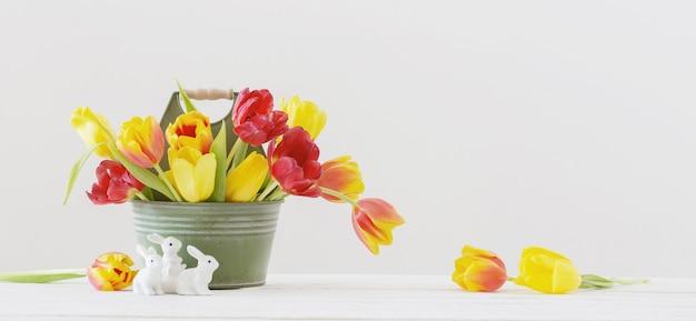 Tulipani rossi e gialli nel secchio e coniglio in ceramica su sfondo bianco