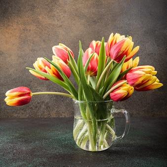 Tulipani gialli rossi in vasi di vetro. un regalo per la festa della donna. biglietto di auguri per la festa della mamma. celebrare la pasqua. copia spazio