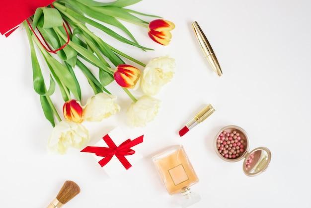 Tulipani rossi e gialli in un sacchetto regalo rosso, cosmetici e regalo su uno sfondo bianco con spazio di copia. biglietto di auguri per san valentino o la festa della mamma. elegante blogger piatto laici