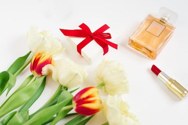 Tulipani rossi e gialli in un sacchetto regalo rosso, rossetto e profumo