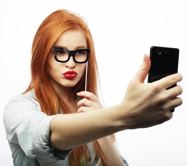 Ragazza dai capelli rossi pronta per la festa, scatta un selfie