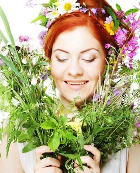 Modello dai capelli rossi con grande acconciatura e fiori tra i capelli e con bouquet di fiori.