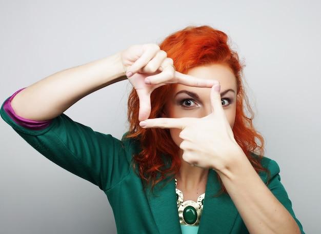 Redhair donna che fa cornice con le mani, tempo felice