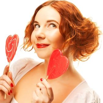 Redhair donna con caramello grande cuore isolato su bianco
