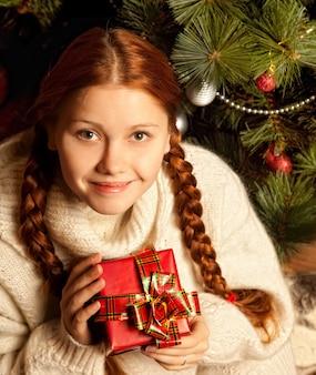Redhair donna con regalo di natale in un interno di una casa