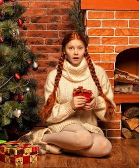 Donna dai capelli rossi con un regalo di natale all'interno di una casa