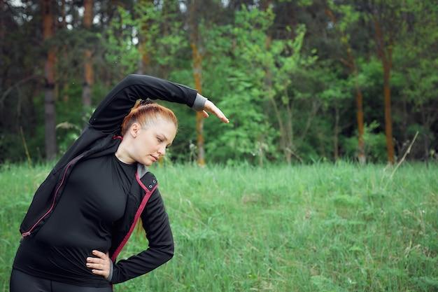 Una donna allegra dai capelli rossi in abiti sportivi fa sport nel parco per perdere peso in eccesso e uno stile di vita sano