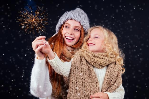 Redhaired donna allo zenzero in cappello caldo e bambina bionda indossare sciarpa lavorata a maglia tenendo bengala sparkler