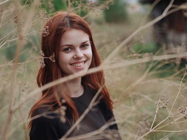 La donna dai capelli rossi in un vestito nero sta camminando sulla natura in autunno nella foresta