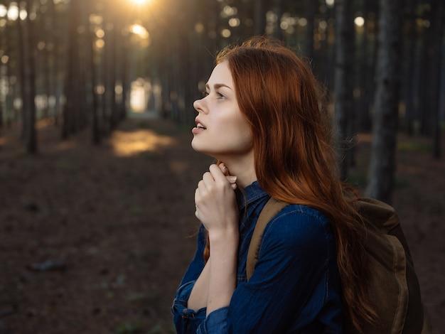 La donna dai capelli rossi nella natura della foresta cammina in libertà