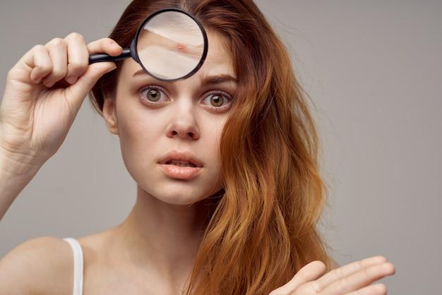 Lente d'ingrandimento della donna dai capelli rossi vicino al primo piano dell'igiene del viso