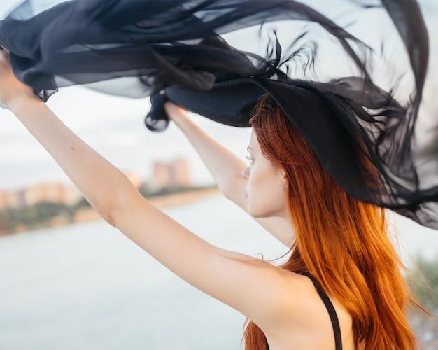 La donna dai capelli rossi e il vestito nero dalla natura camminano alla moda