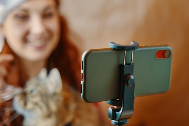Donna dai capelli rossi con gatto comunica tramite collegamento video virtuale parlando con amici collega e usin...