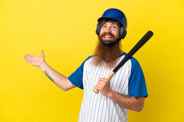 Redhead giocatore di baseball uomo con casco e pipistrello isolato su sfondo giallo che estende le mani di lato per invitare a venire