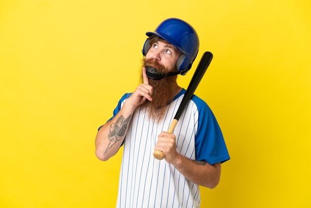 Redhead giocatore di baseball uomo con casco e pipistrello isolato su sfondo giallo guardando in alto mentre sorride