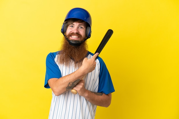 Redhead giocatore di baseball uomo con casco e pipistrello isolato su sfondo giallo che punta indietro