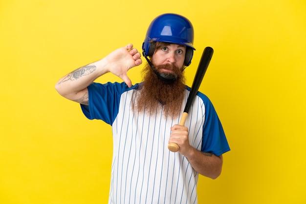 Redhead giocatore di baseball uomo con casco e pipistrello isolato su sfondo giallo che mostra il pollice verso il basso con espressione negativa
