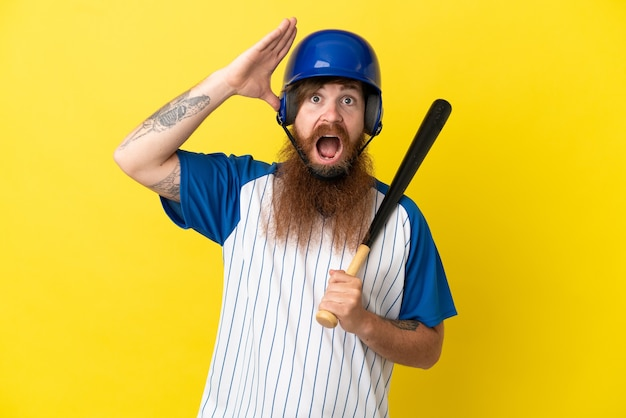 Uomo del giocatore di baseball della testarossa con casco e pipistrello isolato su sfondo giallo con espressione a sorpresa