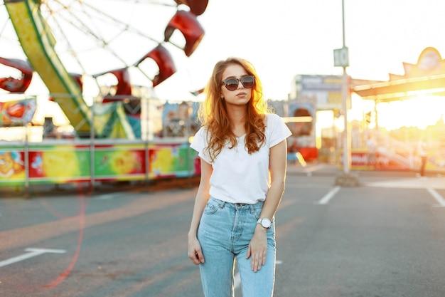 Redhead bella carina giovane donna hipster in maglietta alla moda in jeans alla moda in occhiali da sole alla moda sta camminando in un parco di divertimenti