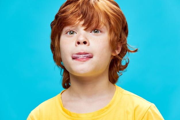 Primo piano del ragazzo della testarossa morde la sua vista ritagliata della parete di autunno divertente della maglietta gialla della lingua
