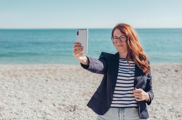Donna d'affari rossa che usa il telefono in riva al mare