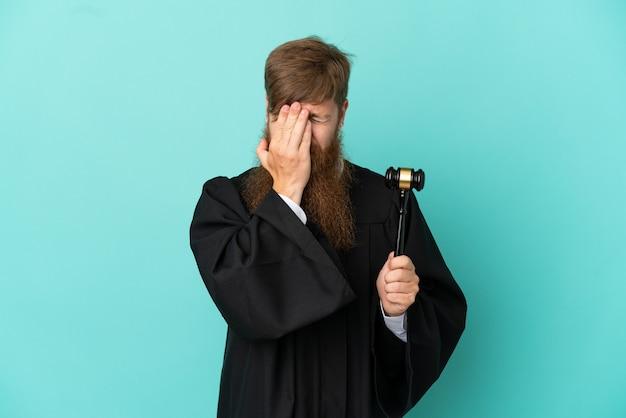 Uomo caucasico del giudice della testarossa isolato su fondo blu con l'espressione stanca e malata