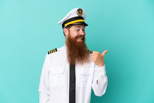 Uomo caucasico dai capelli rossi che gioca a rugby isolato su sfondo giallo rivolto verso il lato per presentare un prodotto